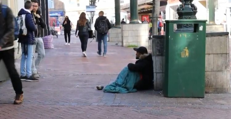 homeless man on a busy street