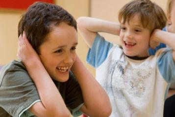 two children laughing with hands on ears