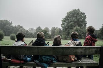 five children sat on a bench with backs to camera
