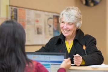lady at a GP reception desk