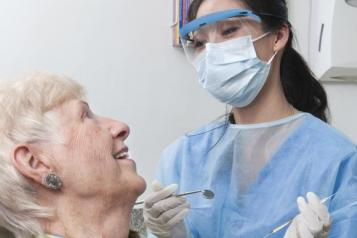 Older lady in a dentist chair smiling at the dentist
