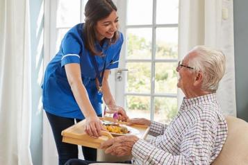 healthcare assistant and an older man in a chair