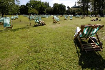 people in the sun on deckchairs