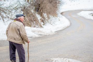 Older man outside walking in the snow
