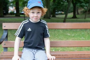 young child sat on a bench