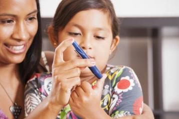 young woman and child with finger prick device