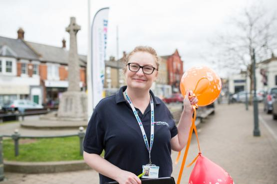 Healthwatch volunteer holding balloons